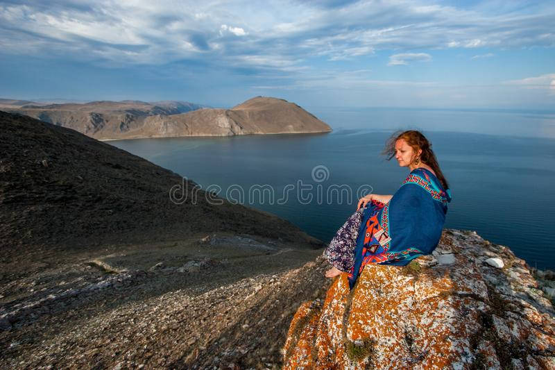 A nice girl in a dress with a colorful scarf on her shoulders sits on a rock by Lake Baikal royalty free stock photography