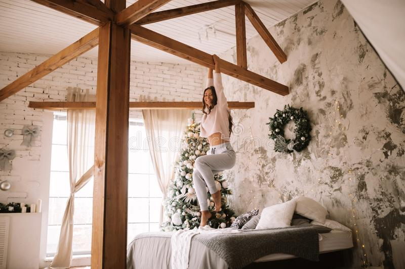 Nice girl dressed in white sweater and pants is hanging on a wooden bar above the bed with gray blanket and white. Pillows in a cozy decorated room with a New stock photography