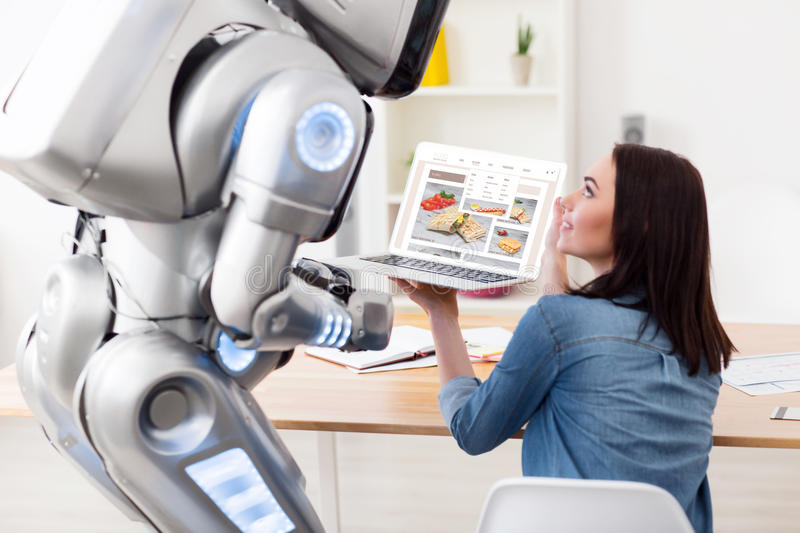 Nice girl holding laptop. Have a look. Pleasant delighted girl sitting at the table and showing screen of the laptop while talking with the robot royalty free stock photography
