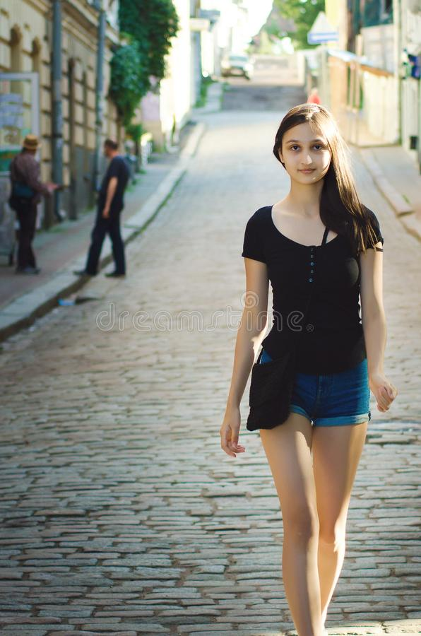 Nice girl with long hair walks down the street with beautiful ancient architecture. Beautiful cityscape royalty free stock photos