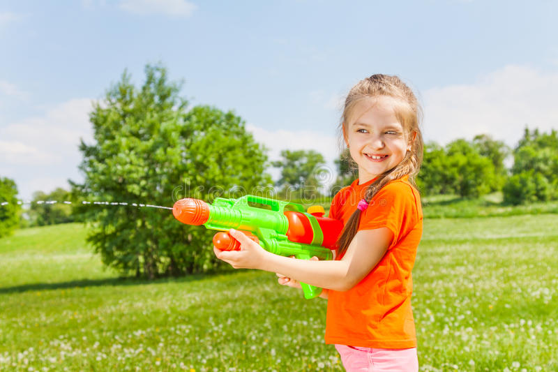 Nice girl playing with water gun. Nice girl shoots a water gun on a green sunny meadow stock photography