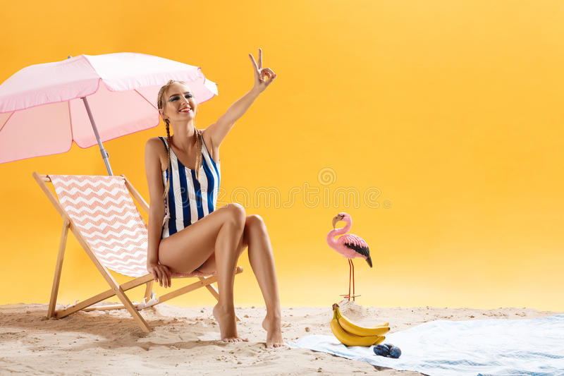 Nice girl posing in swimsuit in studio, showing peace sign. Nice model girl posing in blue and white swimsuit in studio, showing peace sign royalty free stock photos