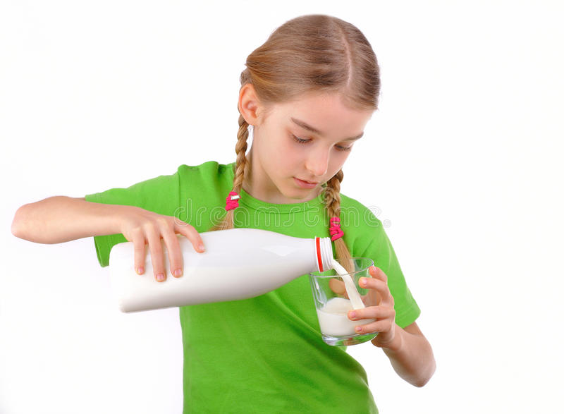 Nice girl pours milk from a bottle into glass. Little blond girl pours milk from a bottle into a glass. Isolated on white background royalty free stock image