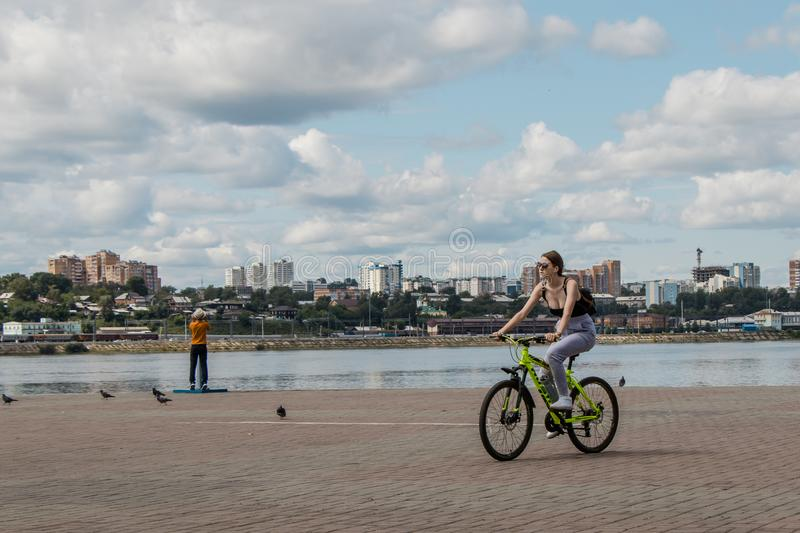 Nice girl rides bicycle along embankment of Angara River against backdrop of city landscape and beautiful cloudy sky. stock photography