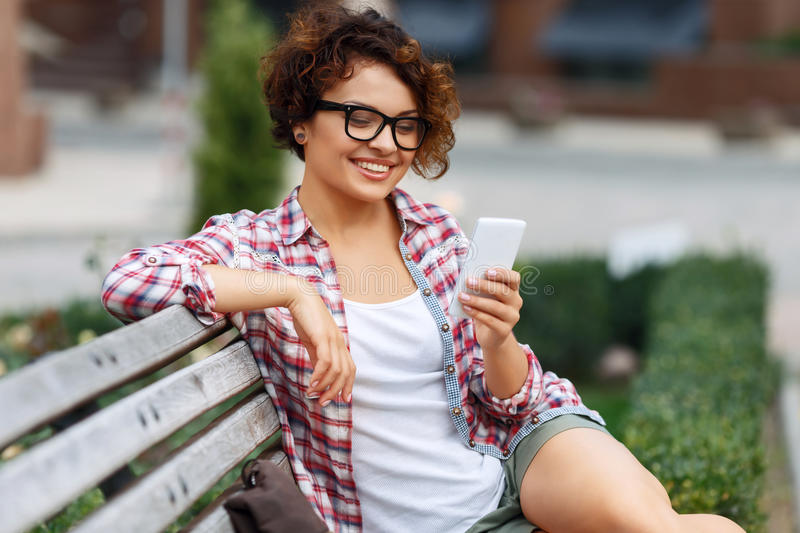 Nice girl sitting on the bench royalty free stock image