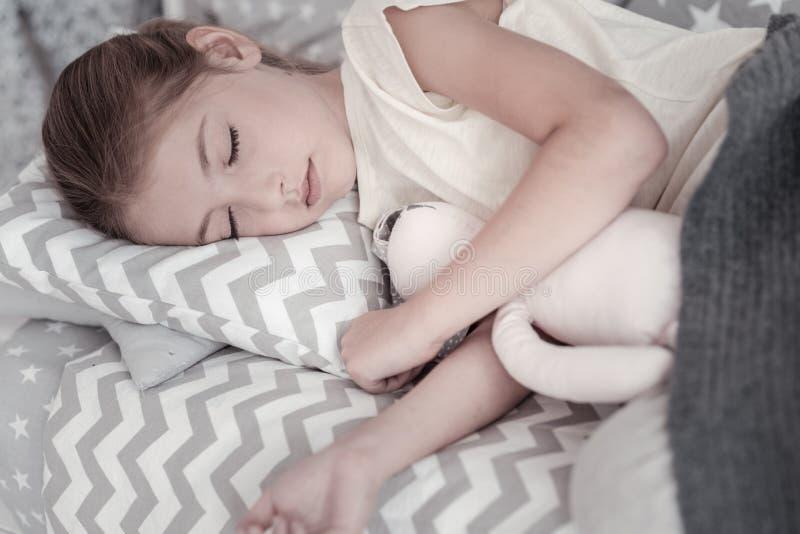 Nice girl sleeping with her toy stock image