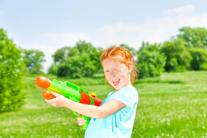 Nice girl with a water gun. Nice girl smiling at camera while playing with water gun on a green meadow royalty free stock photography