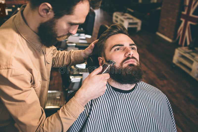 Nice and good hairstylist is cutting some of the customer`s beard with an electrical razer. He is doing that very. Accurate stock images