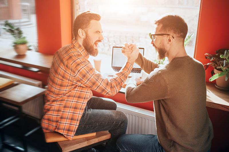 Nice and good picture of two guys sitting at the table in front of the big window and holding each other with that fists stock photo