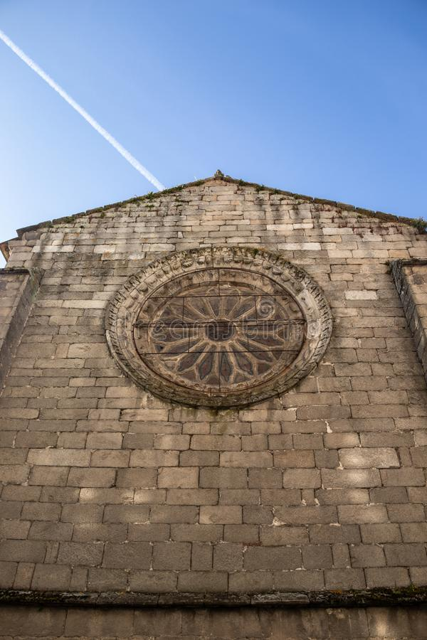 Nice gothic rose window on a stone wall of a church in sunny day. Galician city of Lugo, Spain. Historic building stock photo