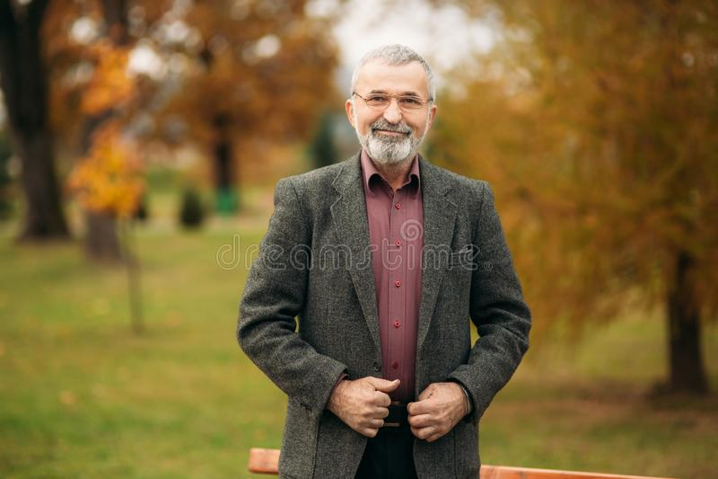 A nice grandfather with a beautiful beard wear a gray jacket royalty free stock photography