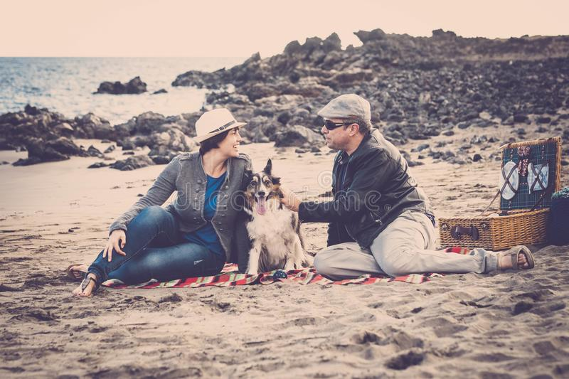 Nice group of dog, man and woman young people having fun together at the beach doing picnic and enjoying the outdoor leisure. Nice group of dog, men and women stock photos