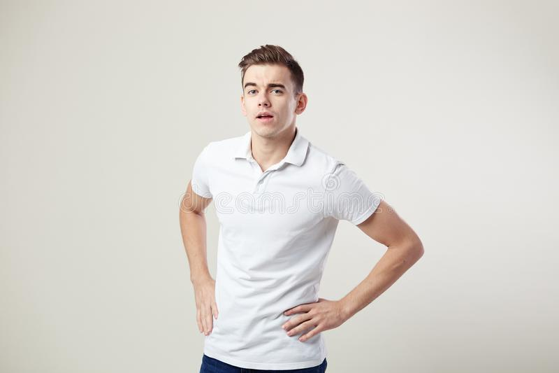 Nice guy dressed in a white t-shirt and jeans keeps his hands on the waist on a white background in the studio stock image