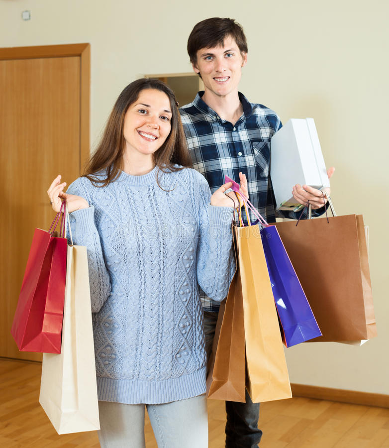 Nice guy and girl holding purchases in hands in home. Nice guy and girl holding purchases in hands at home stock image
