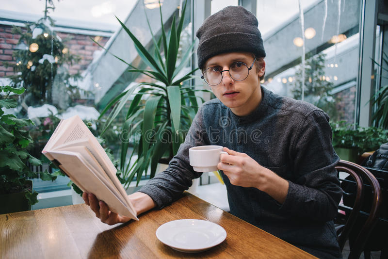 Nice guy hipster glasses and hat reading a book and drinking tea in restaurant. Handsome guy in hipster glasses and hat reading a book and drinking tea in the stock image