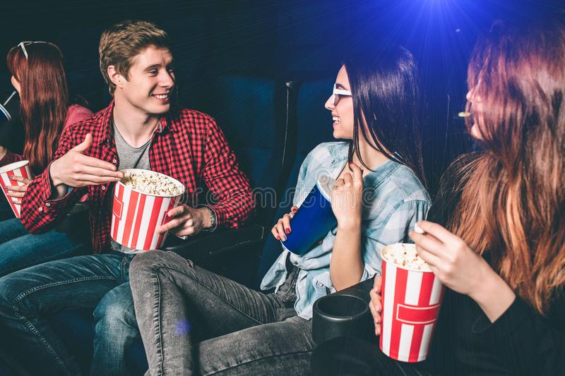 Nice guy is proposing his popcorn to a girl. Two girls are looking at him and smiling. Brunette girl is impressed. She. Is holding a cup of coke while her stock image