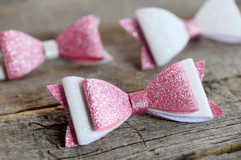 Nice hair bows accessories made of light pink and white felt with sequins. Hair bows for girls on an old wooden table. Closeup stock photos