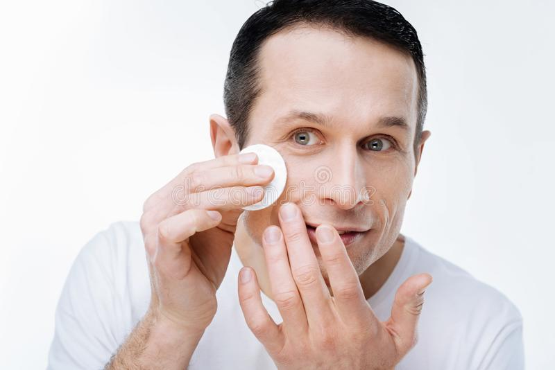 Nice handsome man caring about his skin stock image