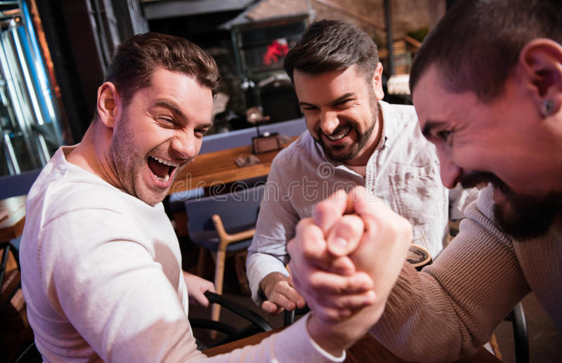 Nice handsome man trying to win the armwrestling match. Tense moment. Nice handsome brutal men looking at his rival and gathering all his strength while trying stock photography