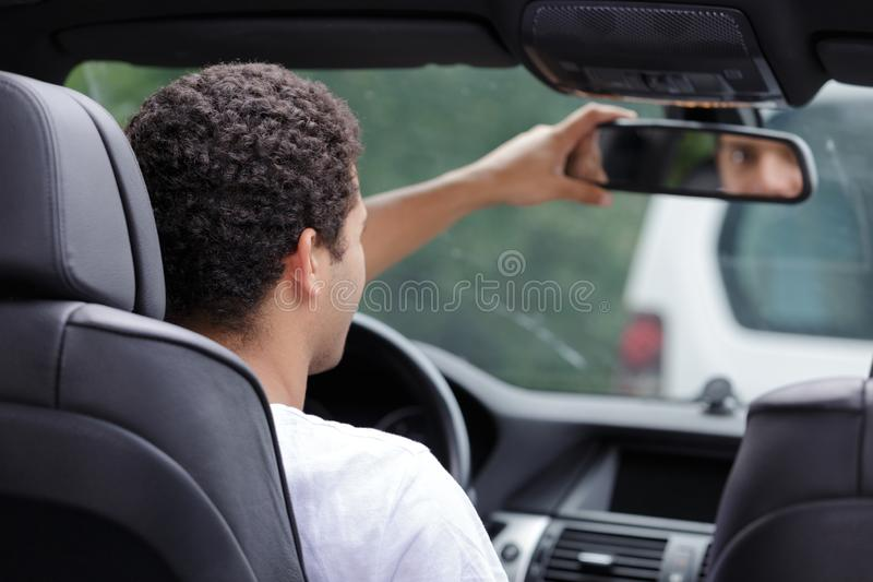 Handsome man fixing rear view mirror stock photo