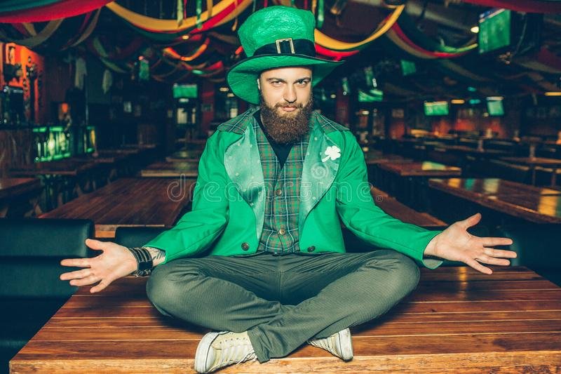 Nice handsome young bearded man in St. Patrick`s suit sit with legs crossed on table in pub. His costume green. Guy pose. royalty free stock images