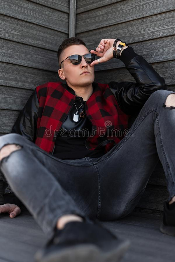Nice handsome young hipster man in black sunglasses in a trendy red checkered jacket in sneakers in gray ripped jeans is sitting royalty free stock photography