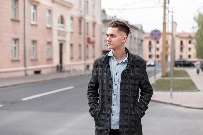 Nice handsome young man with a fashionable hairstyle in a gray luxurious checkered jacket in a shirt walks around the city. Near vintage buildings on a spring stock photos