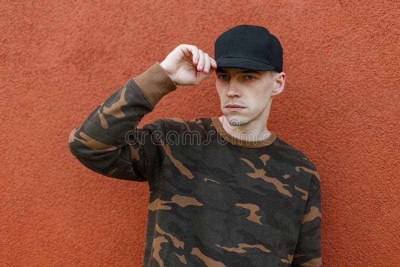 Nice handsome young man in a stylish black cap in a trendy green military shirt posing in the city near a vintage building stock images