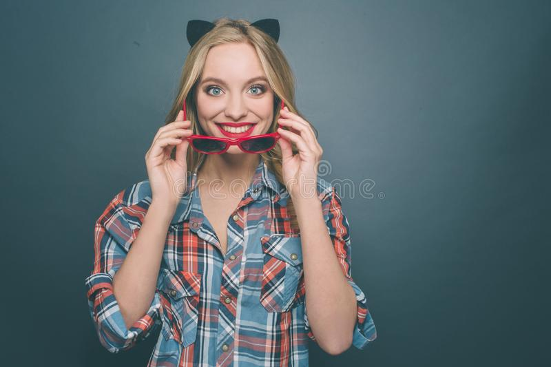 Nice and happy person is wearing grey with red shirt and a kitten ear on her head. Also she is putting on her glasses royalty free stock images