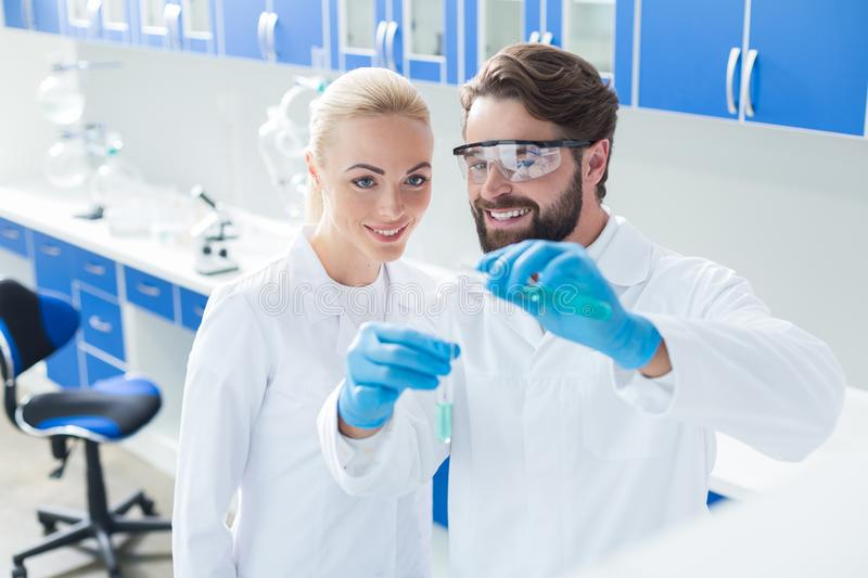 Nice happy scientists looking at the test tubes stock photo