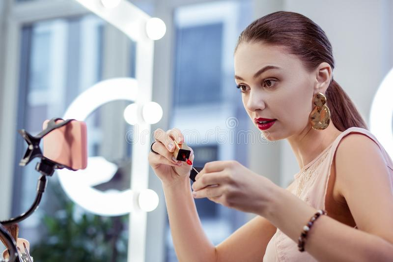 Nice happy woman showing a shiny lipstick. Bright colour. Nice happy woman showing a shiny lipstick while recording a video for her blog stock images