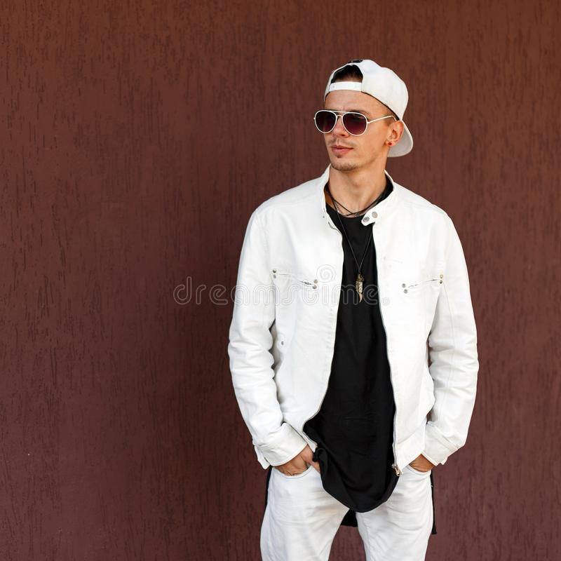 Nice hipster young man in a trendy white summer jacket in a stylish black t-shirt in a fashionable baseball cap in dark sunglasses royalty free stock photos