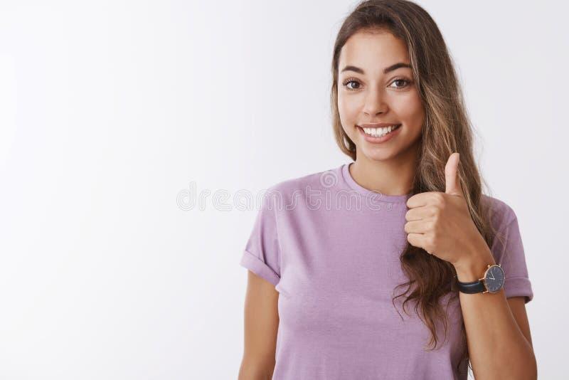 Nice I binnen Vriendschappelijk uitgaand schitterend jong glimlachend meisje die duim tonen die omhoog, het houden goedkeuren van stock foto