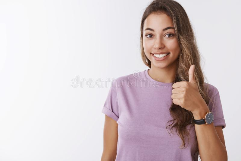 Nice I in. Friendly outgoing gorgeous young smiling girl showing thumb up saying yes, approving liking awesome stock photo