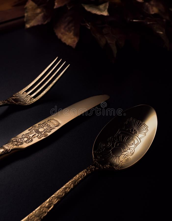 Nice image with spoon, knife, fork and golden accessory on the table stock images