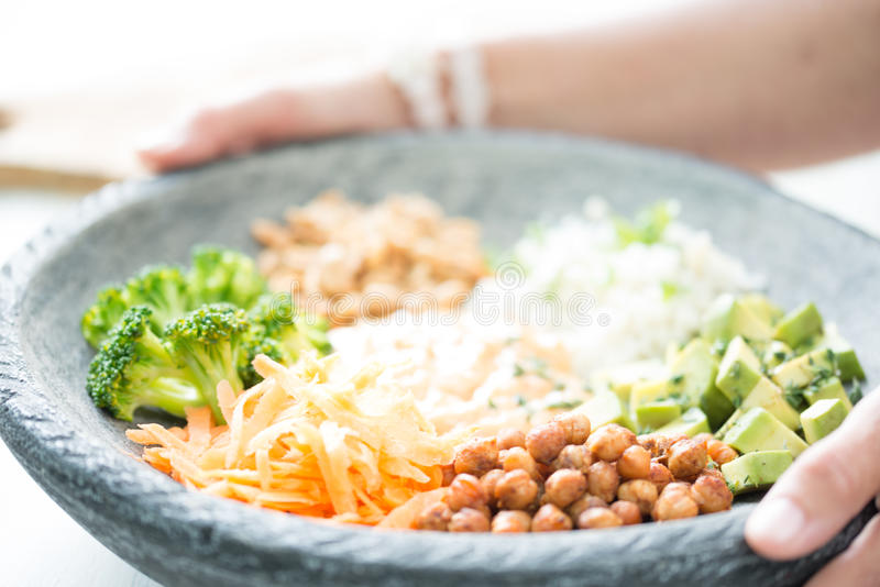 Nice image of a woman serving fresh salad in a buddha bowl. stock photography