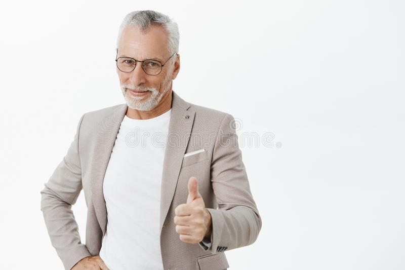 Nice job son. Portrait of proud and pleased good-looking old father in elegant suit and glasses showing thumbs up and. Smiling delighted from good positive stock images