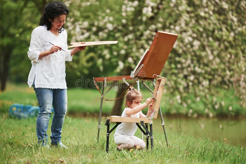 Nice job. Teaching granddaughter how to paint. In the natural parkland.  royalty free stock photos
