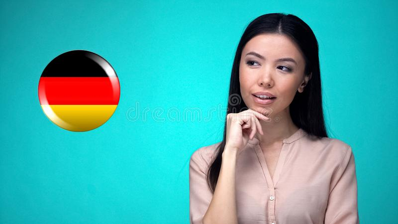 Nice lady looking at German flag sign, international trade company, purchase stock photo
