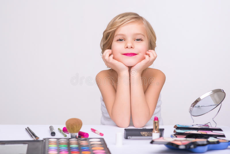 Nice little girl doing make up royalty free stock photo