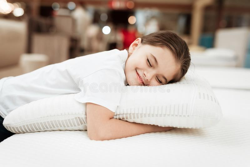 Nice little girl hugs pillow in store of orthopedic mattresses. Testing softness of pillow. royalty free stock image