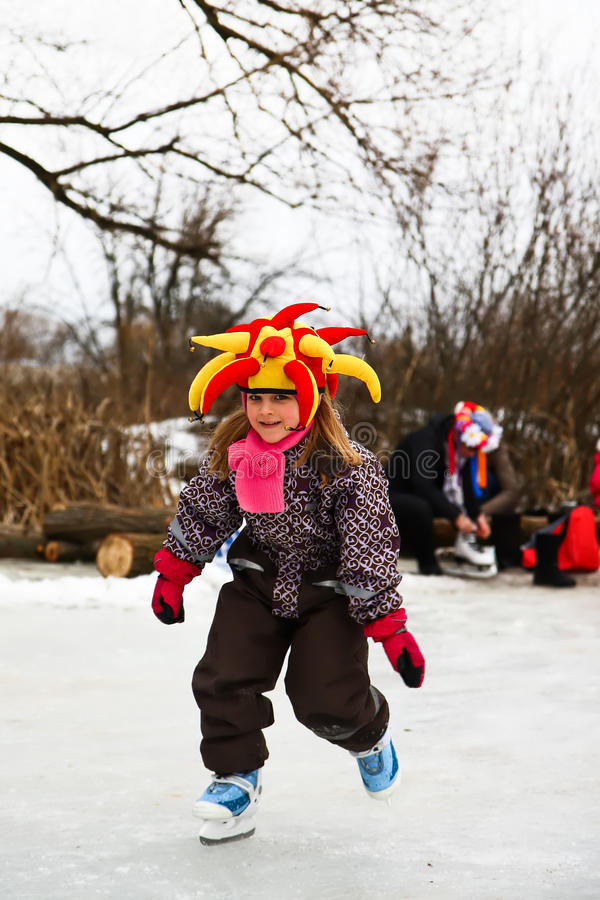 Nice little girl learning ice skating stock images