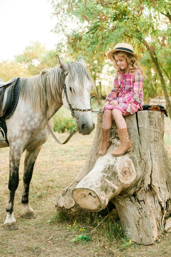 A nice little girl with light curly hair in a vintage plaid dress and a straw hat and a gray horse. Horses a. A nice little girl with light curly hair in a stock photography