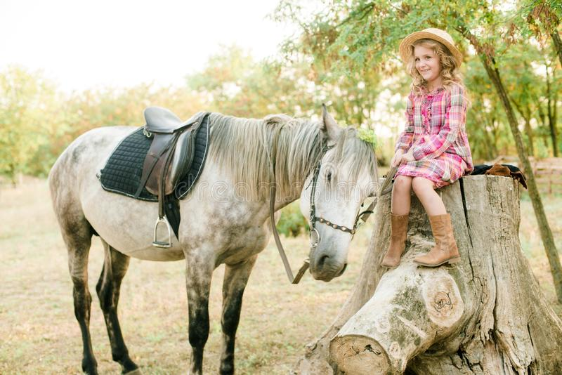 A nice little girl with light curly hair in a vintage plaid dress and a straw hat and a gray horse. Rural life in autumn. Horses and people royalty free stock image