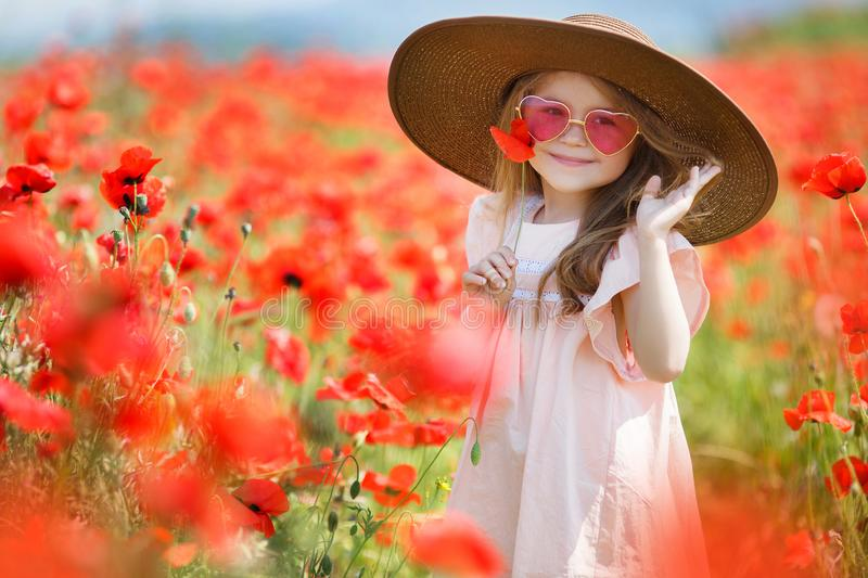 Little girl in big hat on a field of blooming red poppies royalty free stock photos