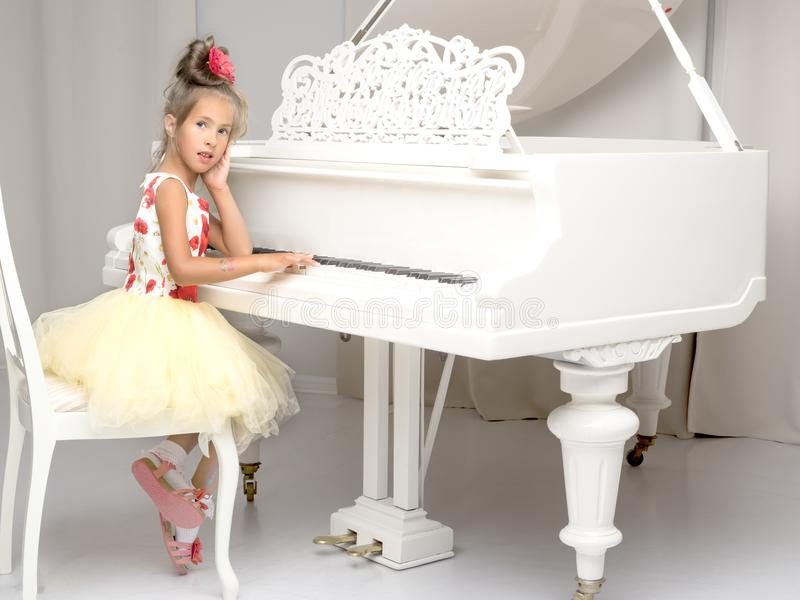 Beautiful little girl is playing on a white grand piano. stock photo