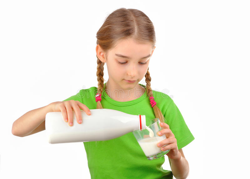Nice little girl pours milk from a bottle into glass. Nice little girl pours milk from a bottle into a glass. Isolated on white background royalty free stock photography