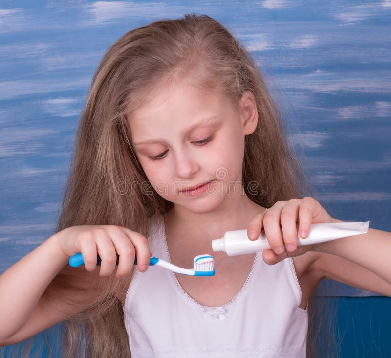 Nice little girl takes care of his teeth, squeezing toothpaste on toothbrush royalty free stock photos