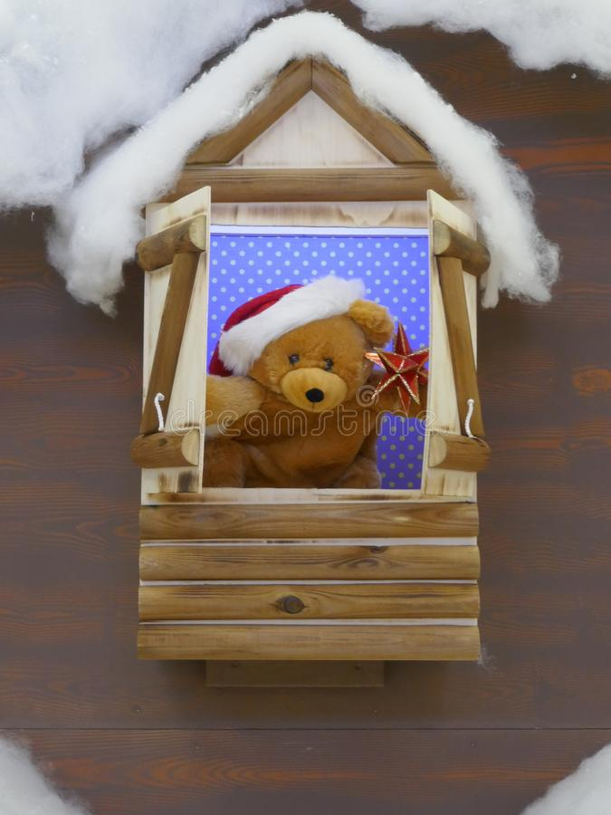 A little plush bear with Santa hat looks out of an open window. A nice little plush bear with Santa hat looks out of an open window royalty free stock images