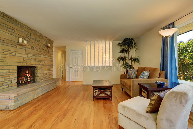 Nice living room in blue and brown colors with stone tile fireplace. royalty free stock image
